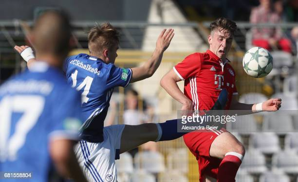 Adrian Fein of FC Bayern Muenchen fights for the ball with Phil Halbauer of FC Schalke 04 during the AJuniors semi final first leg German...