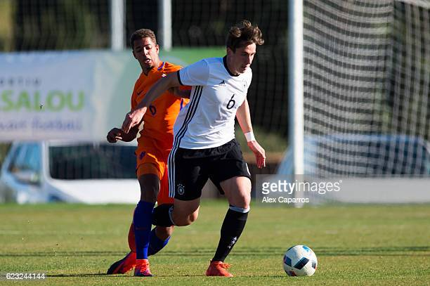Adrian Fein of Germany conducts the ball past Justin Lonwijk of Netherlands during the U18 international friendly match between Netherlands and...