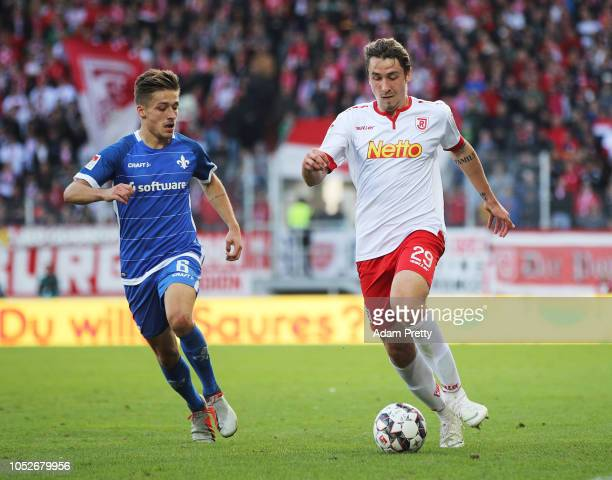 Adrian Fein of Jahn Regensburg controls the ball in front of Marvin Mehlem of SV Darmstadt 98 during the Second Bundesliga match between SSV Jahn...