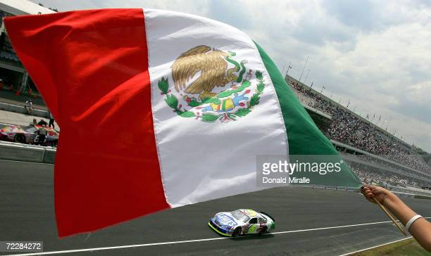 Adrian Fernandez of Mexico drives his Lowe's Chevrolet Monte Carlo as a fan waves the Mexican flag during qualifying for the Telcel Mexico 200 Nascar...