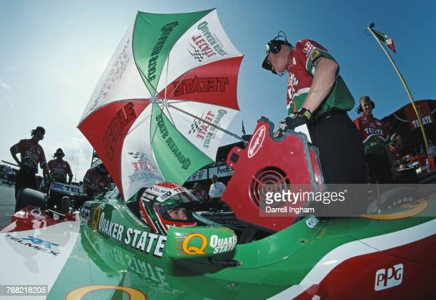Adrian Fernandez of Mexico sits aboard the Tecate Quaker State Fernandez Racing Reynard 01iHonda in the pits during practice for the Championship...