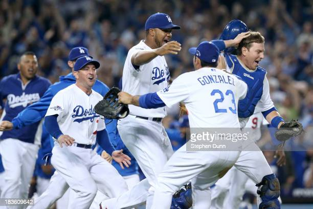 Adrian Gonzalez AJ Ellis and Kenley Jansen of the Los Angeles Dodgers celebrate after the Dodgers defeat the Atlanta Braves 43 in Game Four of the...