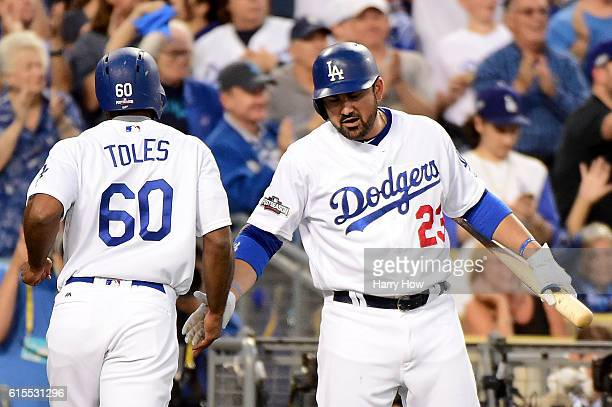 Adrian Gonzalez celebrates with Andrew Toles of the Los Angeles Dodgers after Toles scores a run in the third inning on a hit by Corey Seager against...