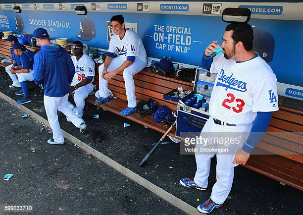 Adrian Gonzalez Jose De Leon and Yasiel Puig of the Los Angeles Dodgers look on fom the dugout during the sixth inning of their MLB game against the...