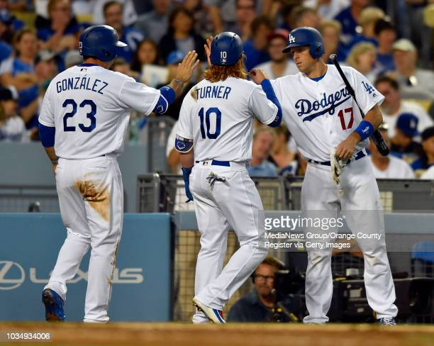 Adrian Gonzalez left and Justin Turner center are congratulated by AJ Ellis after they scored on a double by Trayce Thompson in the 3rd inning in Los...