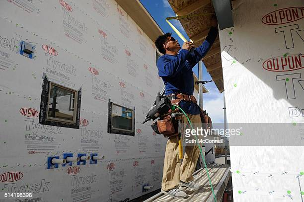 Adrian Gonzalez measures the overhang on a new home as he works to reinforce it and enclose it at the Boulevard One development in Denver Colorado on...