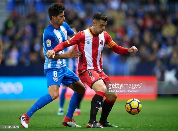Adrian Gonzalez of Malaga CF competes for the ball with Alex Granell of Gerona FC during the La Liga match between Malaga and Girona at Estadio La...