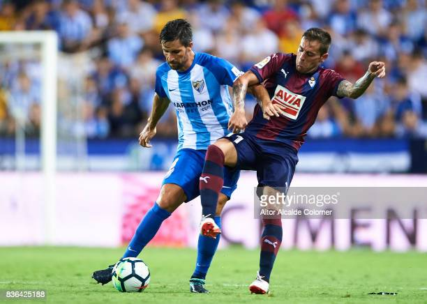 Adrian Gonzalez of Malaga CF competes for the ball with Ruben Pena of SD Eibar during the La Liga match between Malaga and Eibar at Estadio La...