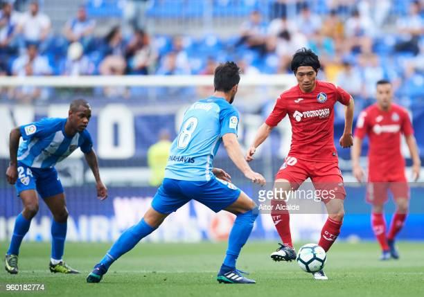 Adrian Gonzalez of Malaga CF duels for the ball with Gaku Shibasaki of Getafe CF during the La Liga match between Malaga CF and Getafe CF at Estadio...
