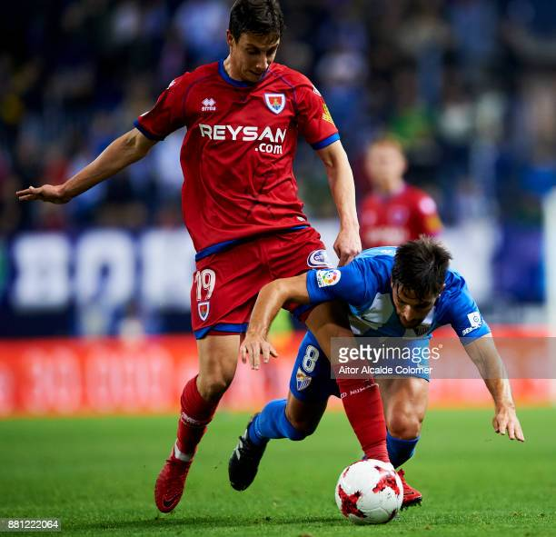 Adrian Gonzalez of Malaga CF duels for the ball with Guillermo Fernandez of Numancia during the Copa del Rey match between Malaga CF and Numancia at...