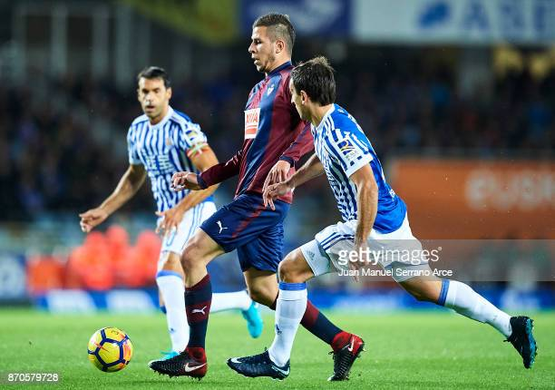 Adrian Gonzalez of SD Eibar being followed by Mikel Oyarzabal and Xabier Prieto of Real Sociedad during the La Liga match between Real Sociedad and...