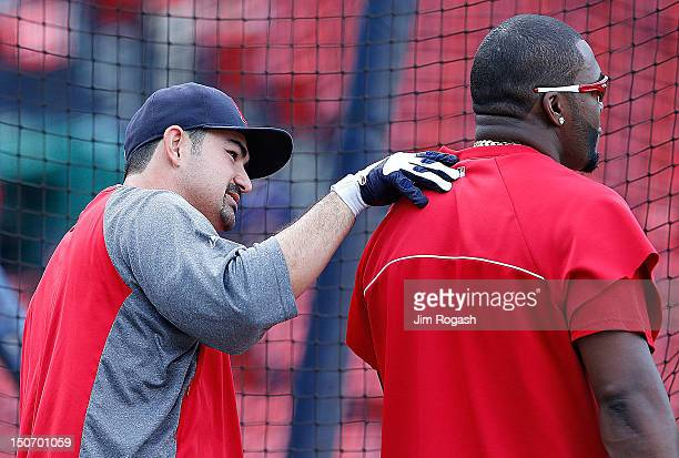 Adrian Gonzalez of the Boston Red Sox shares a moment with David Ortiz at the batting cage before a game with the Kansas City Royals at Fenway Park...