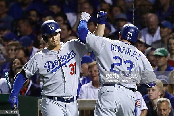 Adrian Gonzalez of the Los Angeles Dodgers celebrates with Joc Pederson after hitting a solo home run in the second inning against the Chicago Cubs...