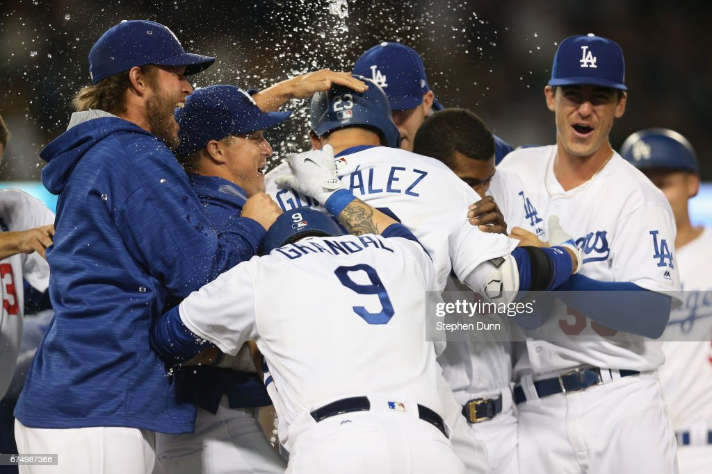 Adrian Gonzalez #23 of the Los Angeles Dodgers is mobbed by teammates including Clayton Kershaw #22 (L) Yasmani Grandal #9, and Cody Bellinger #35 after hitting a walk off RBI infield single the ninth inning to defeat the Philadelphia Phillies at Dodger Stadium on April 29, 2017 in Los Angeles, California. The Dodgers won 6-5.