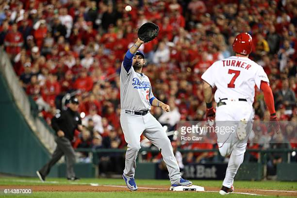 Adrian Gonzalez of the Los Angeles Dodgers makes a catch to force out Trea Turner of the Washington Nationals for the first out of the first inning...