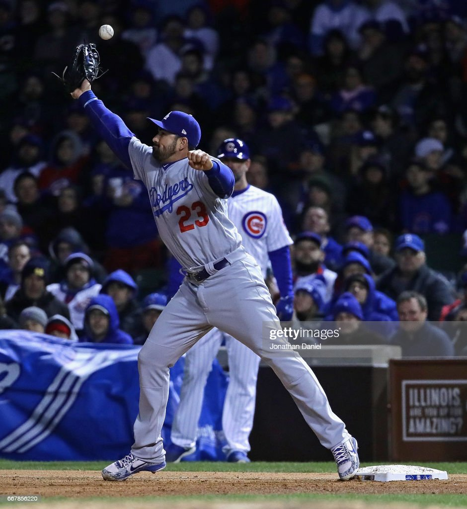 Adrian Gonzalez #23 of the Los Angeles Dodgers misses the throw for an error in the 8th inning against the Chicago Cubs at Wrigley Field on April 12, 2017 in Chicago, Illinois.
