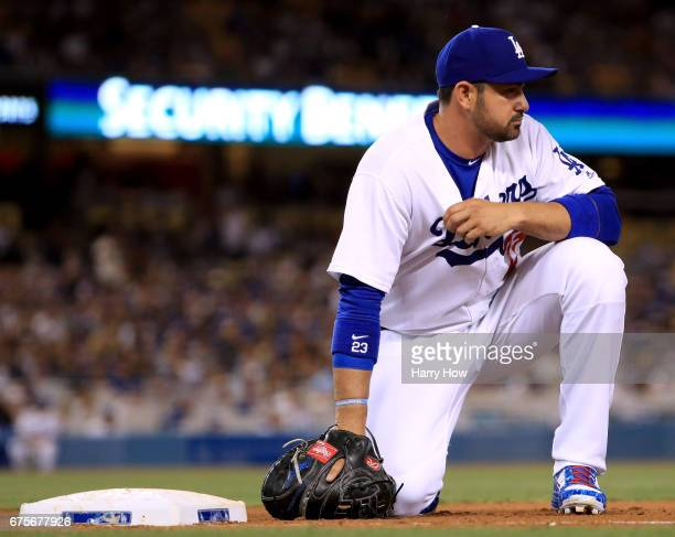 Adrian Gonzalez of the Los Angeles Dodgers reacts to a throwing error from Clayton Kershaw allowing Gorkys Hernandez of the San Francisco Giants to...