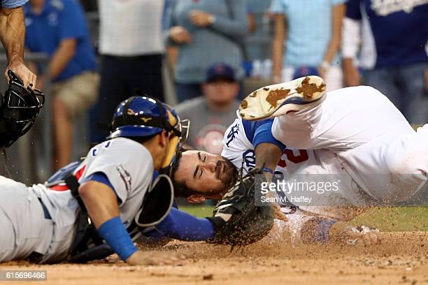 Adrian Gonzalez of the Los Angeles Dodgers slides into home as he attempts to get his left hand under the glove of catcher Willson Contreras of the...