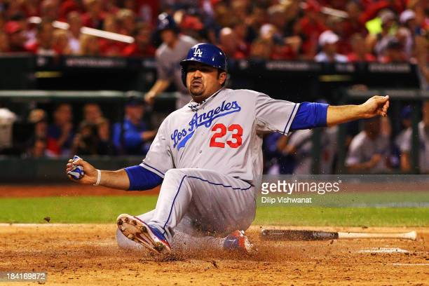 Adrian Gonzalez scores on a two RBI single by Juan Uribe of the Los Angeles Dodgers in the third inning against the St Louis Cardinals during Game...