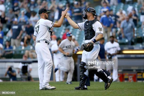 Adrian Houser and Erik Kratz of the Milwaukee Brewers celebrate after beating the New York Mets 176 at Miller Park on May 26 2018 in Milwaukee...