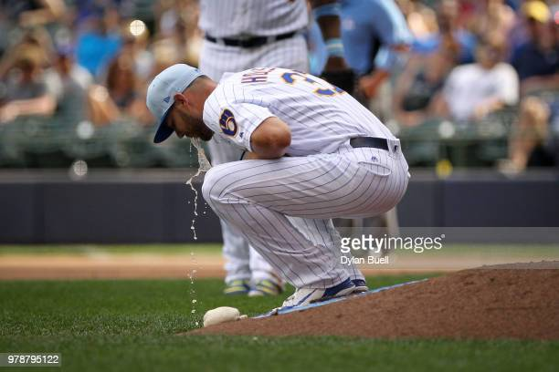 Adrian Houser of the Milwaukee Brewers vomits on the mound in the eighth inning against the Philadelphia Phillies at Miller Park on June 17 2018 in...