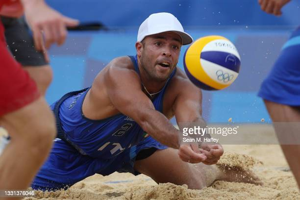 Adrian Ignacio Carambula Raurich of Team Italy dives for the ball against Team Switzerland during the Men's Preliminary - Pool C beach volleyball on...