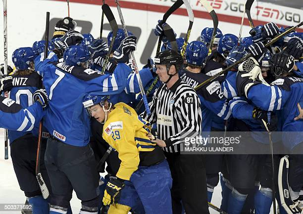 Adrian Kempe of Sweden stands next to Finland's players after the 2016 IIHF World Junior Ice Hockey Championship semifinal match between Sweden and...