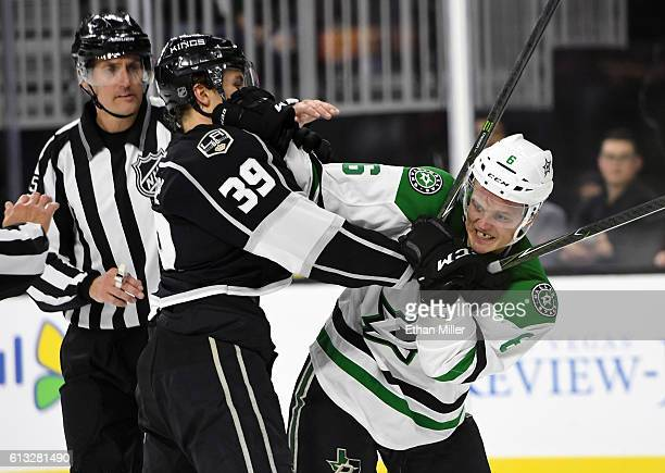Adrian Kempe of the Los Angeles Kings and Julius Honka of the Dallas Stars grab each other as referees move in to separate them during their...