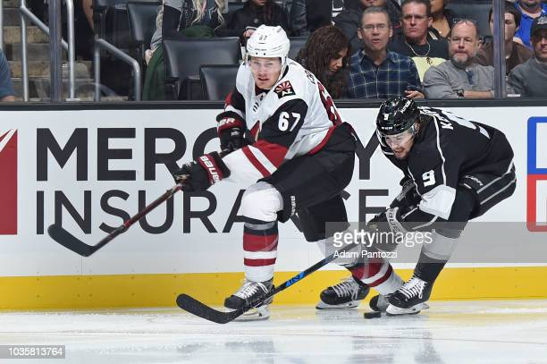 Adrian Kempe of the Los Angeles Kings battles for the puck against Lawson Crouse of the Arizona Coyotes during a preseason game at STAPLES Center on...