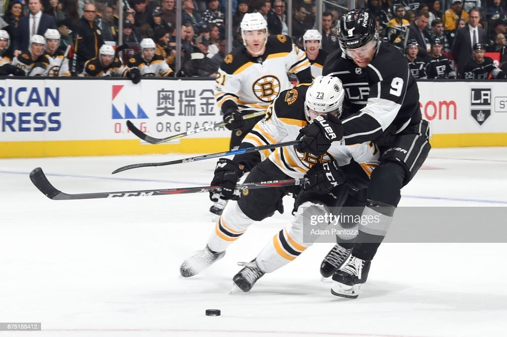 Adrian Kempe #9 of the Los Angeles Kings battles for the puck against Charlie McAvoy #73 of the Boston Bruins at STAPLES Center on November 16, 2017 in Los Angeles, California.
