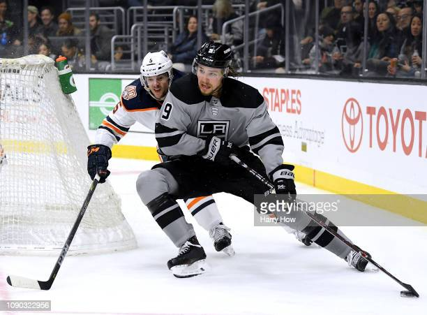 Adrian Kempe of the Los Angeles Kings fends off Kevin Gravel of the Edmonton Oilers as he skates around the net during the second period at Staples...