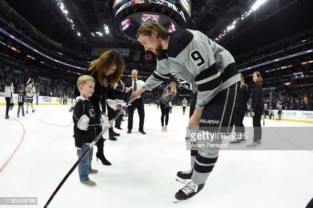 Adrian Kempe of the Los Angeles Kings gives a young fan his hockey stick after the final game of the season against the Vegas Golden Knights during...