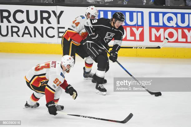 Adrian Kempe of the Los Angeles Kings handles the puck against Matt Bartkowski and Sam Bennett of the Calgary Flames at STAPLES Center on October 11...