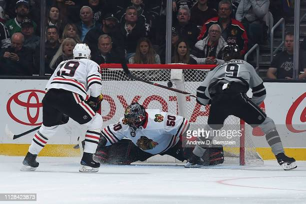 Adrian Kempe of the Los Angeles Kings scores past goaltender Corey Crawford as Jonathan Toews looks on during the second period of the game at...