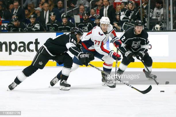 Adrian Kempe of the Los Angeles Kings TJ Oshie of the Washington Capitals and Paul LaDue of the Los Angeles Kings fight for control of the puck at...