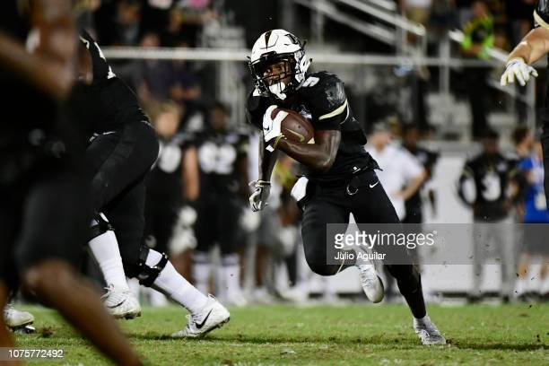 Adrian Killins Jr #9 of the UCF Knights runs for a first down during the fourth quarter of the American Athletic Championship against the Memphis...