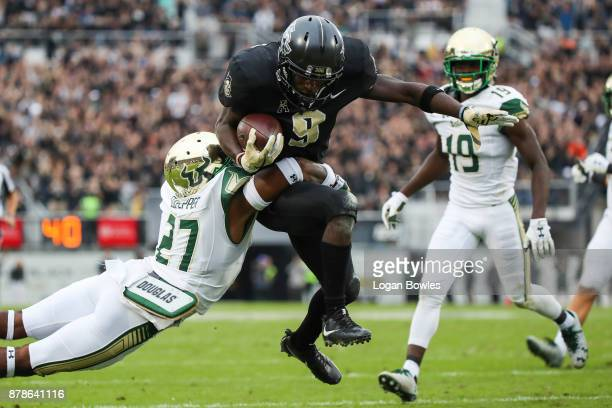 Adrian Killins Jr #9 of the UCF Knights runs the ball for a touchdown in the first quarter as Naytron Culpepper of the South Florida Bulls defends at...