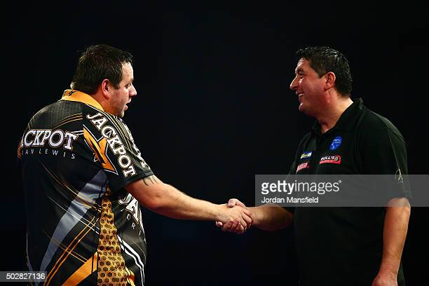 Adrian Lewis of England shakes hands with Mensur Suljovic of Austria after victory in their third round match on Day Eleven of the 2016 William Hill...