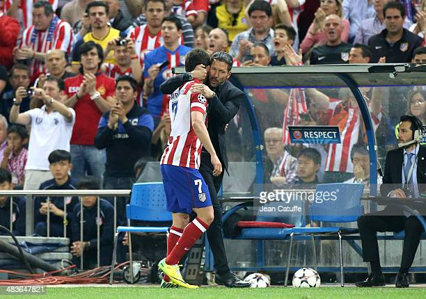 Adrian Lopez Alvarez of Atletico Madrid is congratulated by coach of Atletico Madrid Diego Simeone after being replaced during the UEFA Champions...
