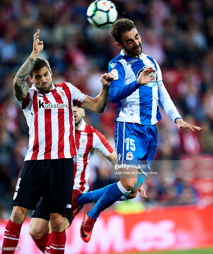 Adrian Lopez of RC Deportivo La Coruna competes for the ball with Inigo Martinez of Athletic Club during the La Liga match between Athletic Club Bilbao and RC Deportivo La Coruna at San Mames Stadium on April 14, 2018 in Bilbao, Spain.