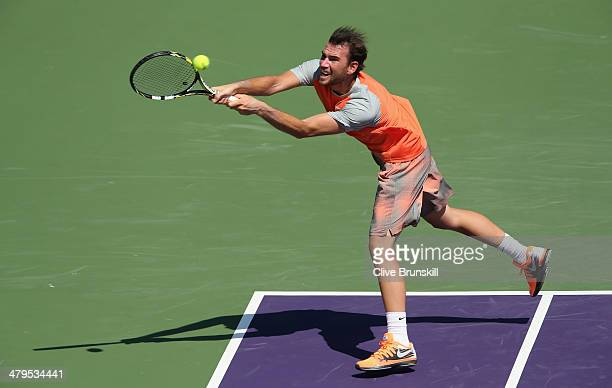 Adrian Mannarino of France plays a backhand against Nikolay Davydenko of Russia during their first round match during day 3 at the Sony Open at...