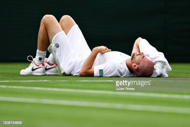 Adrian Mannarino of France reacts as he goes down with an injury in his Men's Singles First Round match against Roger Federer of Switzerland during...
