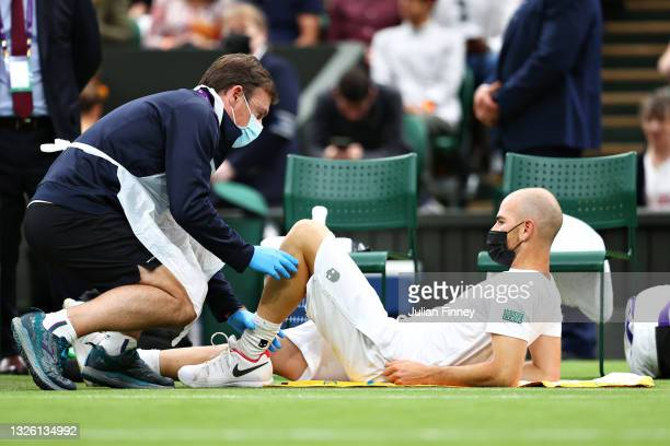 Adrian Mannarino of France receives medical treatment in his Men's Singles First Round match against Roger Federer of Switzerland during Day Two of...
