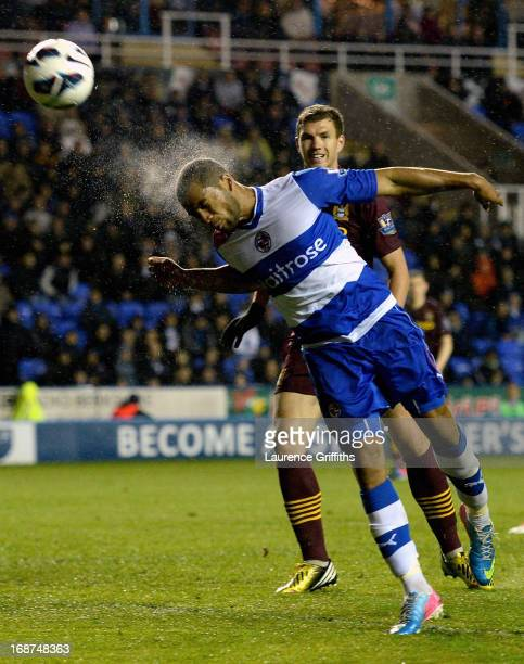 Adrian Mariappa of Reading heads the ball clear as the rain pours during the Barclays Premier League match between Reading and Manchester City at the...