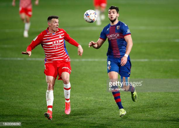 Adrian Marin Gomez of Granada CF battles for possession with Rafa Mir of SD Huesca during the La Liga Santander match between SD Huesca and Granada...