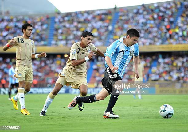 Adrian Martinez of Argentina runs for the ball with Aly Fathy of Egypt during the FIFA U20 World Cup Colombia 2011 round of 16 match between...