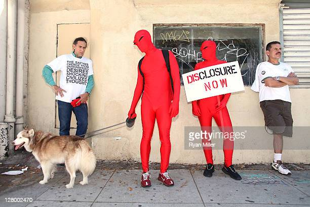 Adrian Massey , Samuel Cormier wait on the sidewalk during the Trespass Parade through downtown Los Angeles and ending at the Museum of Contemporary...