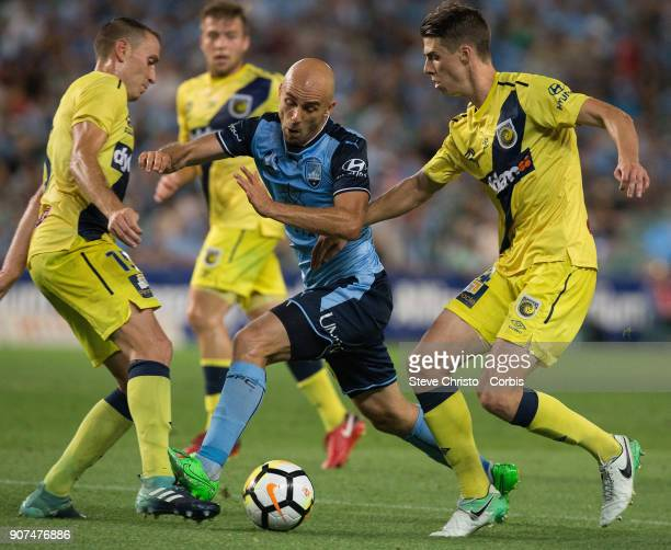 Adrian Mierzejewski of Sydney FC is stuck between Mariners Alan Baro Calabuig and Jake McGing during the round 17 ALeague match between Sydney FC and...