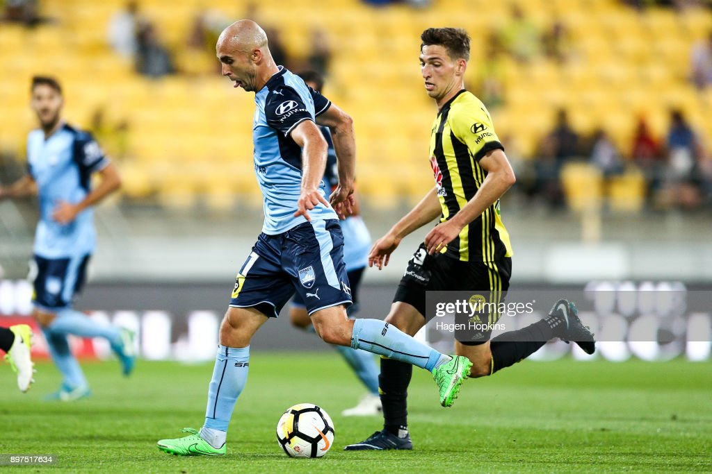 Adrian Mierzejewski of Sydney FC makes a break from Matthew Ridenton of the Phoenix during the round 12 A-League match between the Wellington Phoenix and Sydney FC at Westpac Stadium on December 23, 2017 in Wellington, New Zealand.
