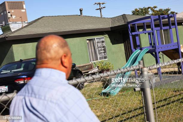 Adrian Miranda, a farm worker originally from Puebla, Mexico, looks at a message, scribbled on a window of a home, dedicated to Breonna Taylor as he...